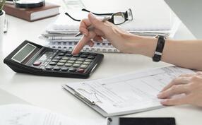 A person typing into a calculator at a desk.